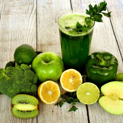 Green smoothies and fruit on a wood background