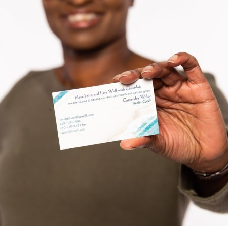 Cassandra holding her business card